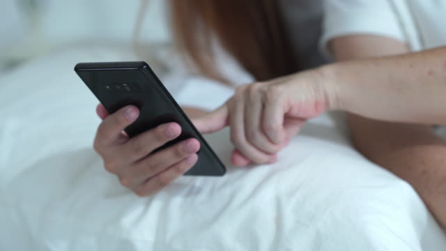 woman hand using phone in bedroom - gossip stock videos & royalty-free footage