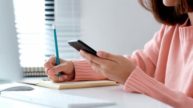 vídeos y material grabado en eventos de stock de mano de mujer con teléfono inteligente y escribir en el cuaderno en el escritorio en la habitación, educación, negocios, vida de la oficina, trabajar en casa concepto - organizador electrónico