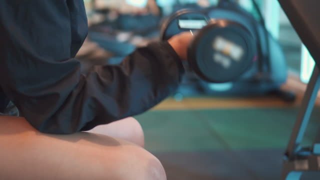Woman hand weight with a dumbbell at gym