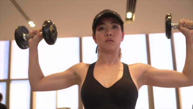 Woman hand weight with a dumbbell in health club
