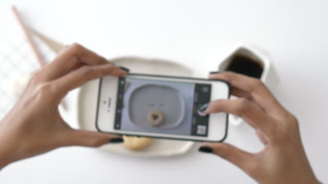 woman hand while using smart phone trying to snap cookie on white table,close up - stock video - trapped stock videos & royalty-free footage