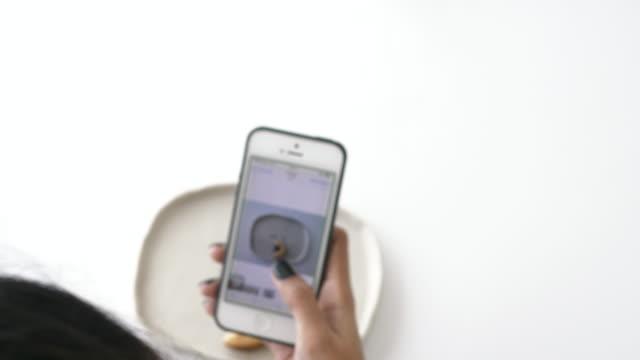 vídeos de stock, filmes e b-roll de mão de mulher enquanto estiver usando o telefone esperto tentando estalar o cookie na mesa branca, close-up - stock vídeo - sobre os ombros