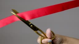A woman hand with gold scissors cutting red ribbon