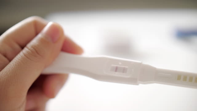 negative positive pregnancy test in hand