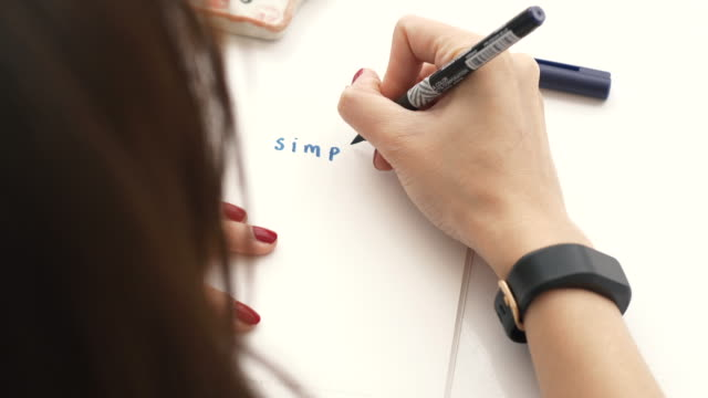 Woman hand with red nail while drawing and writing her work on the table in her room