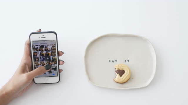 Woman hand with touching smart phone while eating some heart of cookie  to present the signage of love; valentine's day concept and smart phone technology