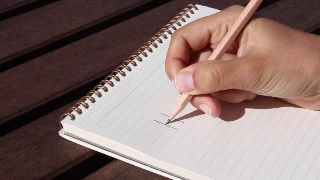 vídeos de stock, filmes e b-roll de uma mão de mulher escreve ajuda com um lápis em um bloco de notas - note pad