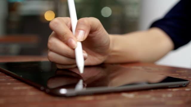 女性の手が彼女のタブレットでビジネス プランを書く - ペン点の映像素材/bロール