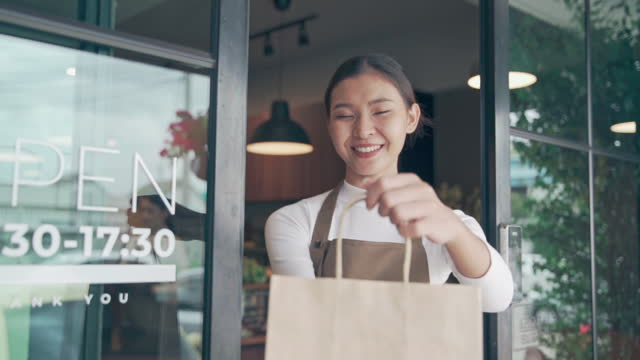 woman handing food and drink bag to customer - 2009 stock videos & royalty-free footage