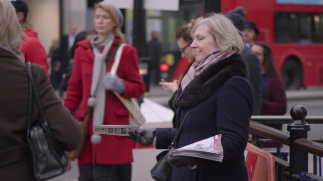 vídeos de stock, filmes e b-roll de woman handing out magazines, oxford circus - bolsa tiracolo bolsa
