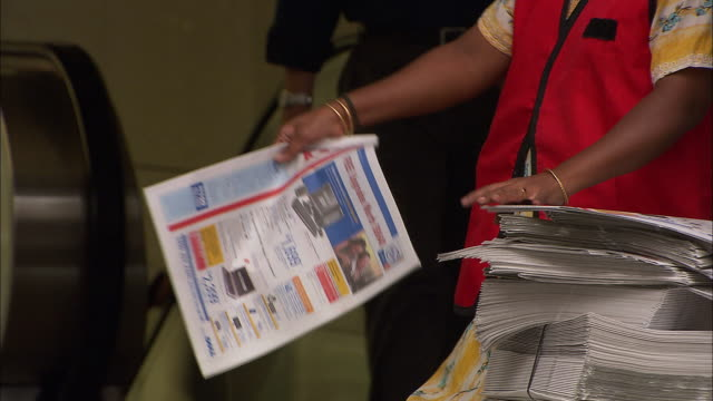 cu, woman handing out newspapers to people on street, mid section, singapore - giving stock videos & royalty-free footage