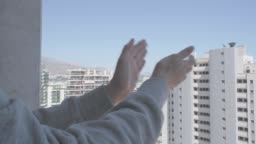 Woman hands applauding medical staff from their balcony. People in Spain clapping gratitude on balconies and windows in support of health workers, doctors and nurses during the Coronavirus pandemic