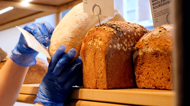 woman hands arrange bread in bakery shop. - french bakery stock videos & royalty-free footage