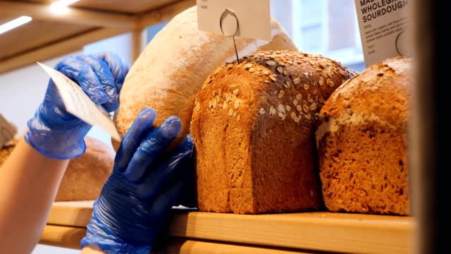 frau in händen arrangiert brot im bäckereigeschäft. - straßenverkäufer stock-videos und b-roll-filmmaterial