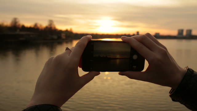 Woman hands capturing memories with phone.