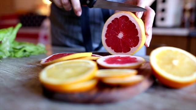 stockvideo's en b-roll-footage met vrouw handen snijden grapefruit - rijp voedselbereiding