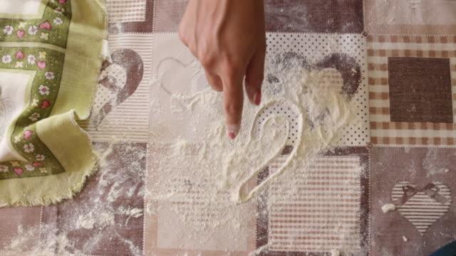 vídeos y material grabado en eventos de stock de manos de mujer dibujando la forma del corazón de la harina en la mesa - al horno