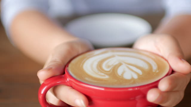 vídeos de stock, filmes e b-roll de mulher com as mãos segurando uma xícara de café no café café - barista