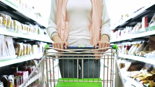 Woman hands holding and pushing a shopping cart, while walking down the aisle