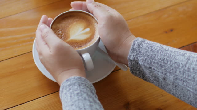 Woman Hands Holding Latte art coffee on wooden table , dolly shot.