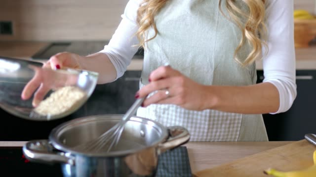 woman hands mixing oats into the boiling water - oatmeal for breakfast - putting stock videos and b-roll footage