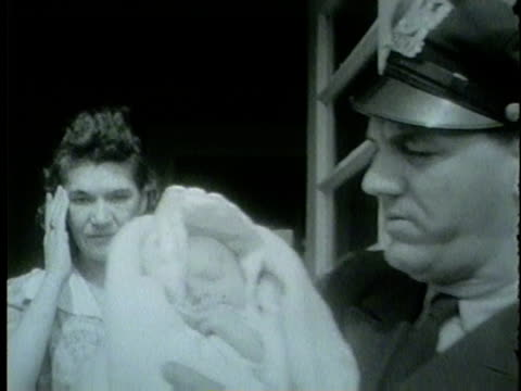 vidéos et rushes de wgn woman hands over baby to cook county sheriff officer in march 1955 - 1955