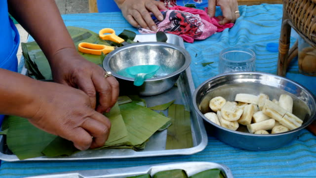 vídeos de stock e filmes b-roll de woman hands packing bananas with glutinous rice steamed in banana leaf - ramo parte de uma planta