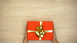 Woman hands putting gift box on wooden background, holiday celebration, top view