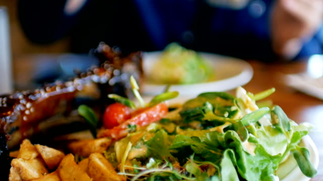 Woman hands take a salad ready for eating on dish with steak