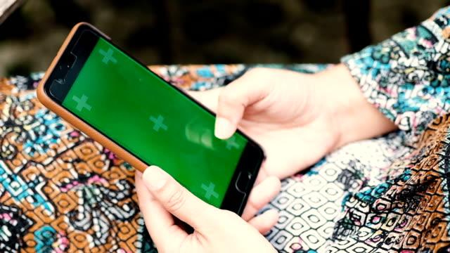 vídeos de stock, filmes e b-roll de mãos de mulher tocando smartphone com tela verde exibir - send