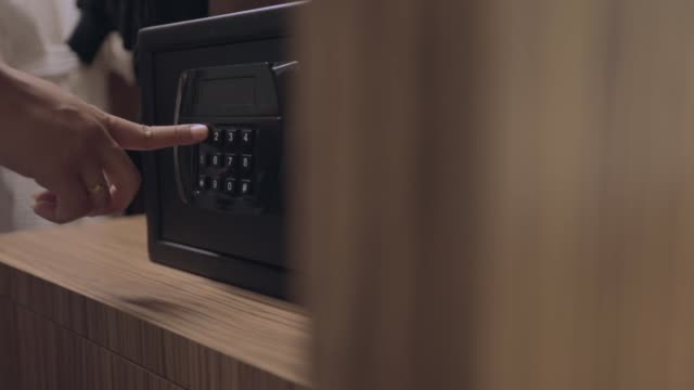vidéos et rushes de combinaison de déverrouillage de mains de femme au coffre-fort dans la chambre d'hôtel, ralenti - document