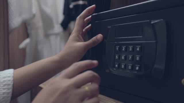 Manos de mujer desbloqueo combinación a caja fuerte en la habitación del hotel, cámara lenta