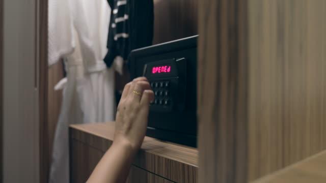 Mujer manos desbloqueo combinación de caja fuerte en la habitación del hotel