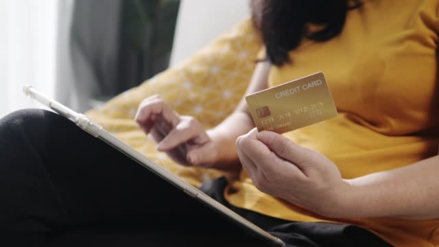 woman hands using digital table and credit card for online shopping at home. - yellow stock videos & royalty-free footage