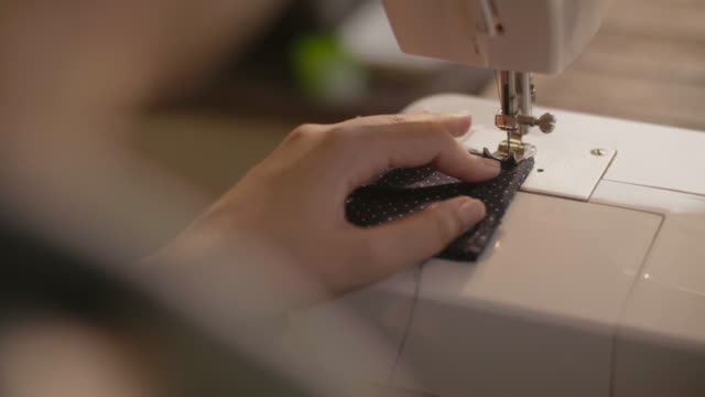 woman hands using the sewing machine to sew the face medical mask during the coronavirus pandemia. home made diy protective mask against virus. - sewing stock videos & royalty-free footage
