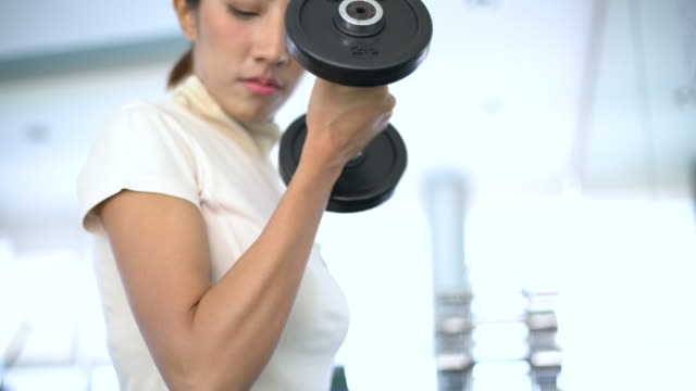 Woman hands weight with a dumbbell in health club