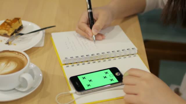 stockvideo's en b-roll-footage met vrouw handen schrijven in notitieblok in koffie cafe met koffie, taart en smartphone, 4k(uhd) - dagboek