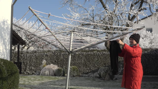 stockvideo's en b-roll-footage met woman hang up clothes to dry in garden in winter - hangen