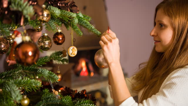 Woman hanging christmas ornaments on tree