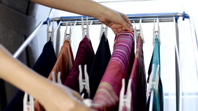 vídeos y material grabado en eventos de stock de mujer colgando ropa con pestillo - estar colgado