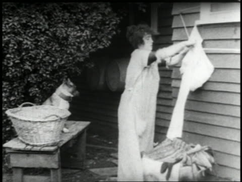 stockvideo's en b-roll-footage met b/w 1915 woman (mabel normand) hanging clothing onto clothesline outside of home with dog - 1915