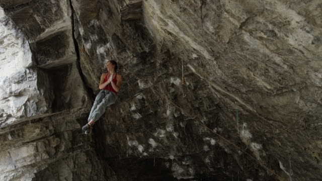 woman hanging from ceiling of cave while rock climbing and chalking hands / american fork canyon, utah, united states - american fork canyon stock videos & royalty-free footage