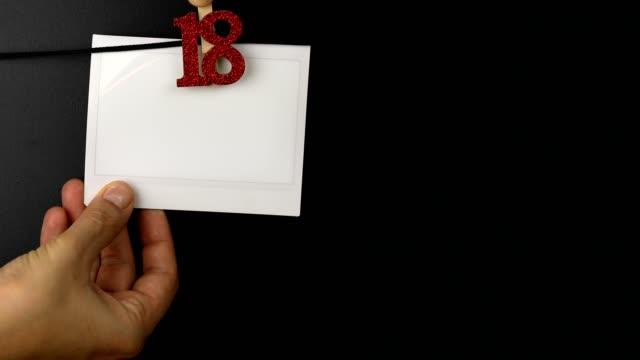 vídeos y material grabado en eventos de stock de mujer colgando marco de fotos instantánea en una cuerda - 18 cumpleaños - transferencia de impresión instantánea