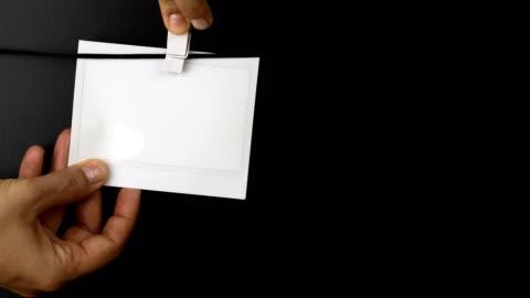 vídeos y material grabado en eventos de stock de mujer colgando marco de fotos instantánea en una cuerda - transferencia de impresión instantánea