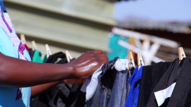 cu woman hanging laundry / cosmo city, south africa - dissolvenza in chiusura video stock e b–roll