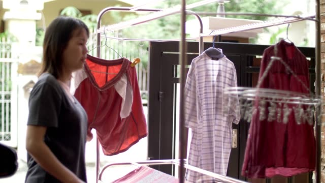 woman hanging laundry on balcony - men's underpants stock videos and b-roll footage