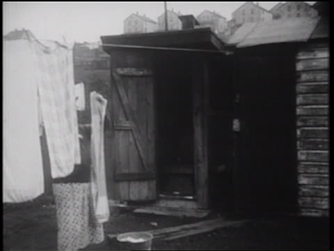 b/w 1939 woman hanging laundry on clothesline as boy enters outhouse / documentary - toilet stock videos and b-roll footage