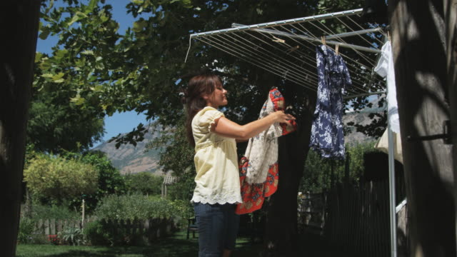 woman hanging laundry to dry - washing line stock videos and b-roll footage