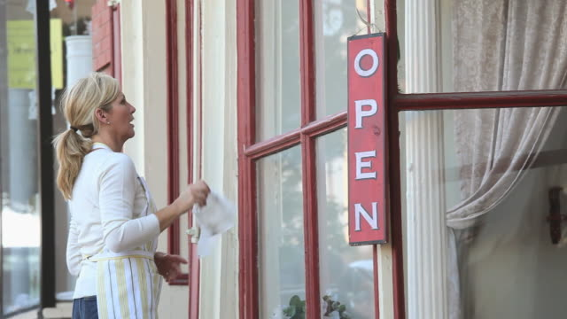 ms pan woman hanging 'open' sign outside shop door, cleaning window, petersburg, virginia, usa - window display stock videos and b-roll footage