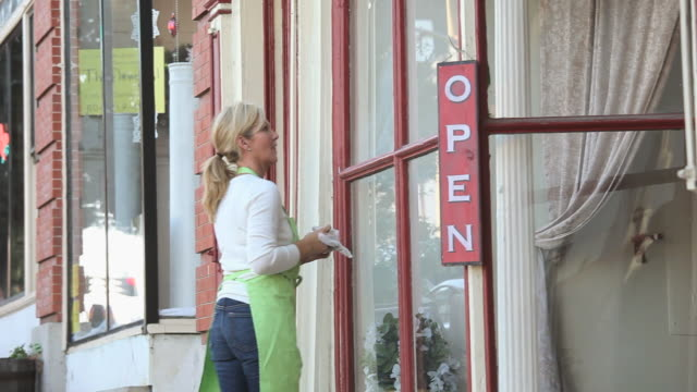 ms pan woman hanging 'open' sign outside shop door, cleaning window, petersburg, virginia, usa - hanging sign stock videos and b-roll footage
